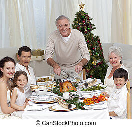Grandfather cutting turkey for Christmas dinner for his...