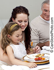 Mother and daughter eating with their family at home -...