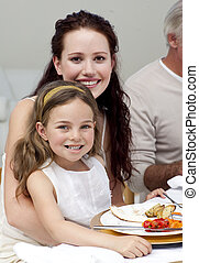 Mother and daughter having dinner with their family at home