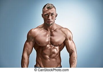 Attractive male body builder on blue background - torso of...