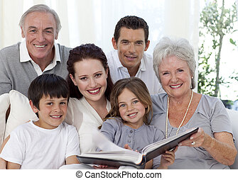 Smiling family looking at a photograph album at home