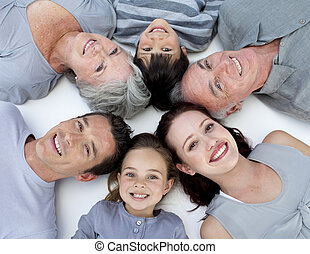 High angle of family lying on floor with heads together -...