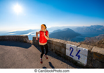 Woman running on the mountain road - Young woman running on...