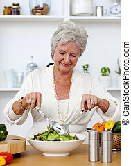 Happy senior woman cooking a salad in the kitchen