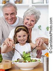 Smiling grandparents eating a salad with granddaughter in...