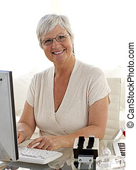 Smiling senior woman working with a computer