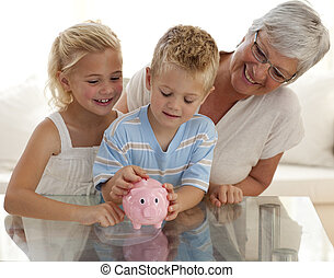 Grandmother and children saving money in a piggybank -...