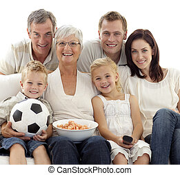Family watching a football match at home - Family eating...