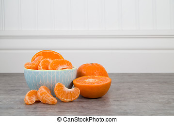 Mandarin orange slices in a blue bowl on a wooden table with...