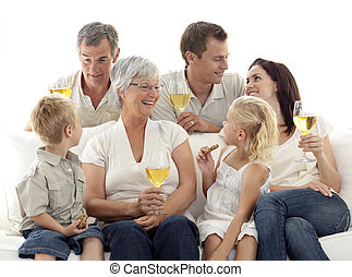 Family in living-room drinking wine and eating biscuits -...