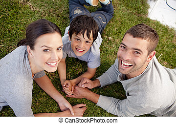 Family lying on garden with hands together