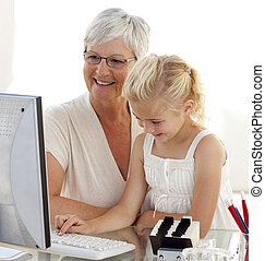 Granddaughter using a computer with her grandmother at home