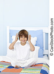 Little boy listening to music in his bed - Happy little boy...