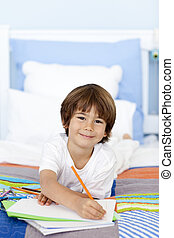 Smiling little boy drawing in bed with colorful pencils