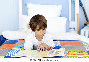 Little boy reading in bed - Little boy reading a book in bed