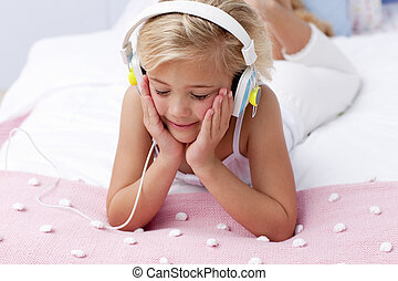 Little girl listening to the music in bed with headphones -...