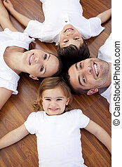 Family lying on floor with heads together - High angle of...