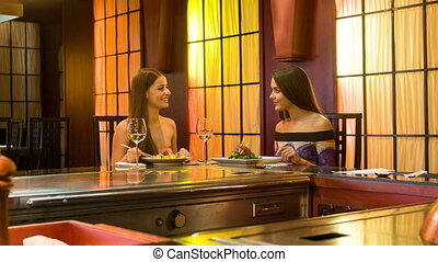 Two smiling young women sitting in stylish Japanese restaurant