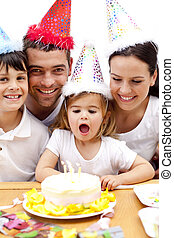 Little girl blowing out candles in her birthday\'s day with family