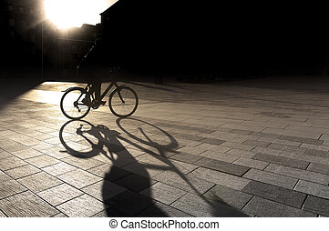 Back lit cyclist at sunset on square in city, with focus on...