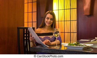 Attractive young smiling woman sitting at table in chic restaurant