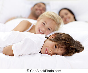 Family resting in parent\'s bed - Young family resting...