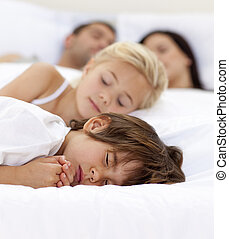 Young family sleeping in parent\'s bed