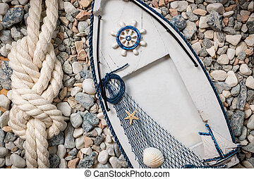 photo frame in shape of boat lying on pebbles