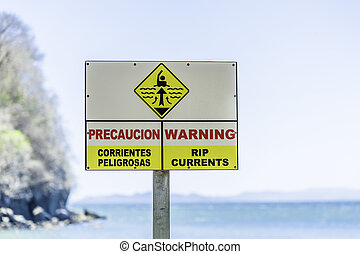 Rip Currents - Warning sign for rip currents near an ocean...