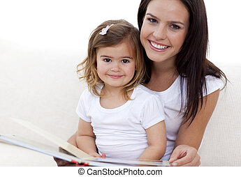 Portrait of mother and daughter reading a book