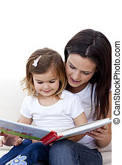 Mother and daughter reading a book on sofa