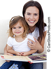 Young mother and daughter reading a book in living-room