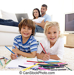Children drawing in living-room and parents on sofa -...