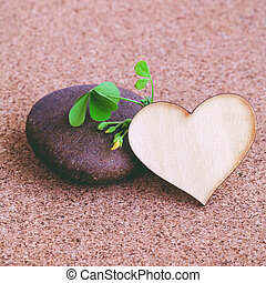 Closeup clover leaf and stone ,wooden heart on cork...