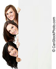Three girls see through white wall - portrait of three...