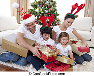 Happy family opening Christmas presents at home