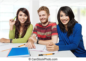 Three smiling students studying together