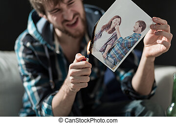 Burning photo with ex-girlfriend - Angry young man burning...