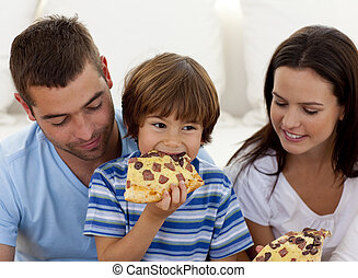 Happy boy eating pizza with ihs parents