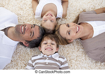 Family lying on floor with heads together - Smiling family...