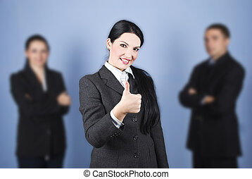 Business woman leader giving thumbs up in the middle of her...