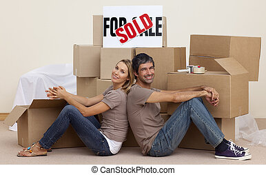 Wife and husband relaxing on floor unpacking boxes after...