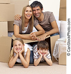 Family in new house playing with boxes - Smiling family in...