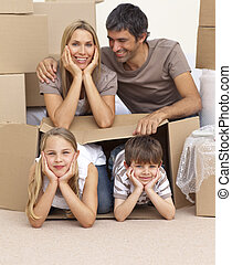 Family moving house playing with boxes - Happy family moving...