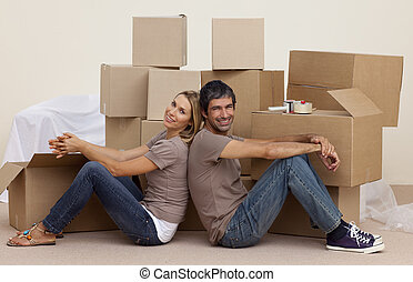Smiling couple sitting on floor around boxes at home