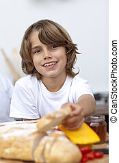 Smiling child eating bread in the kitchen