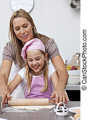 Mother and daughter baking cookies in the kitchen