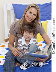 Attractive mother reading a book with her son