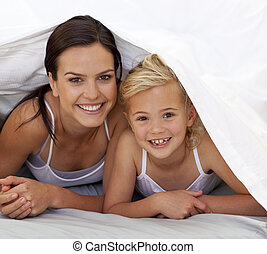 Mother and daughter under the bedsheets - Mother and...