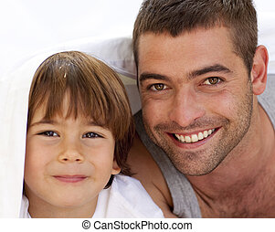 Portrait of dad and son under the bedsheets - Portrait of...